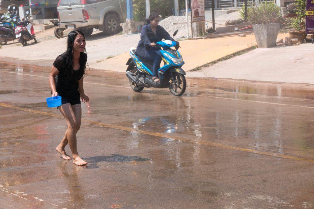 Tropfnasse Frau auf der Straße während Songkran auf Koh Lanta