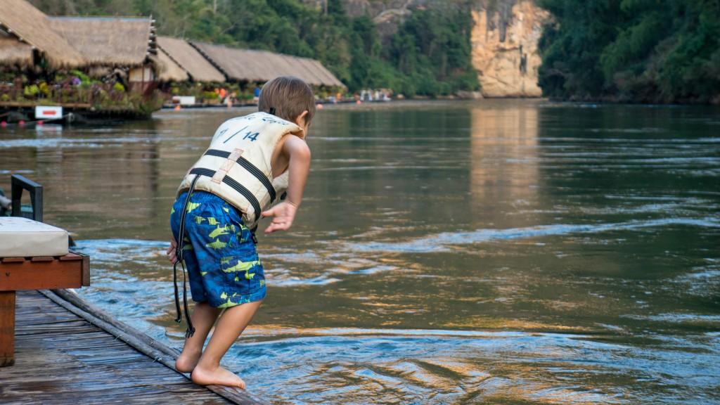 Kleiner Junge mit Rettungsweste springt in den Kwai