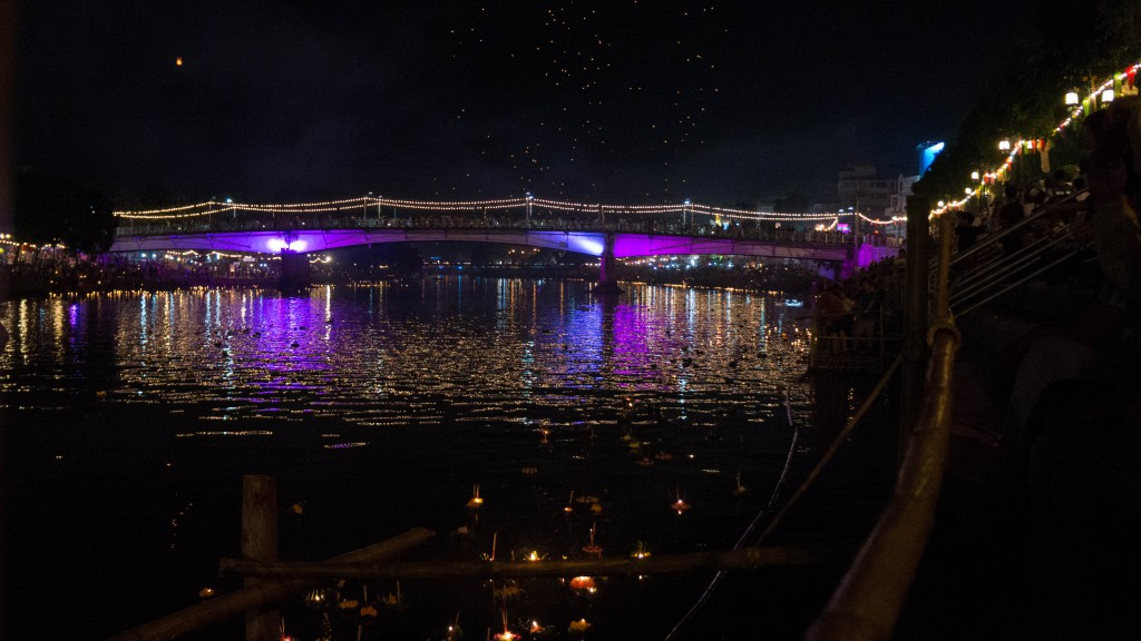 Auf dem Ping River schwimmen leuchtende Boote, während im Hintergrund Himmelslaternen steigen.