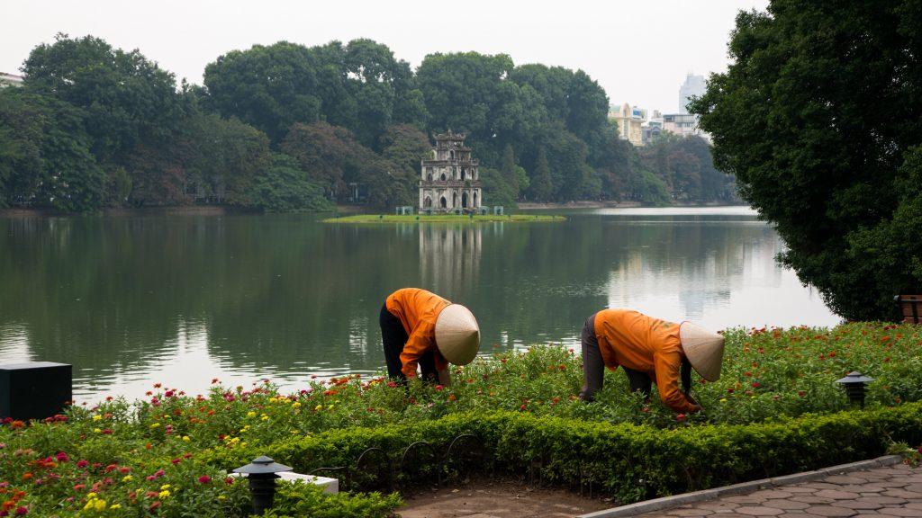 Arbeiterinnen mit typischem Reishut in Hanoi vor dem Turtle Tower