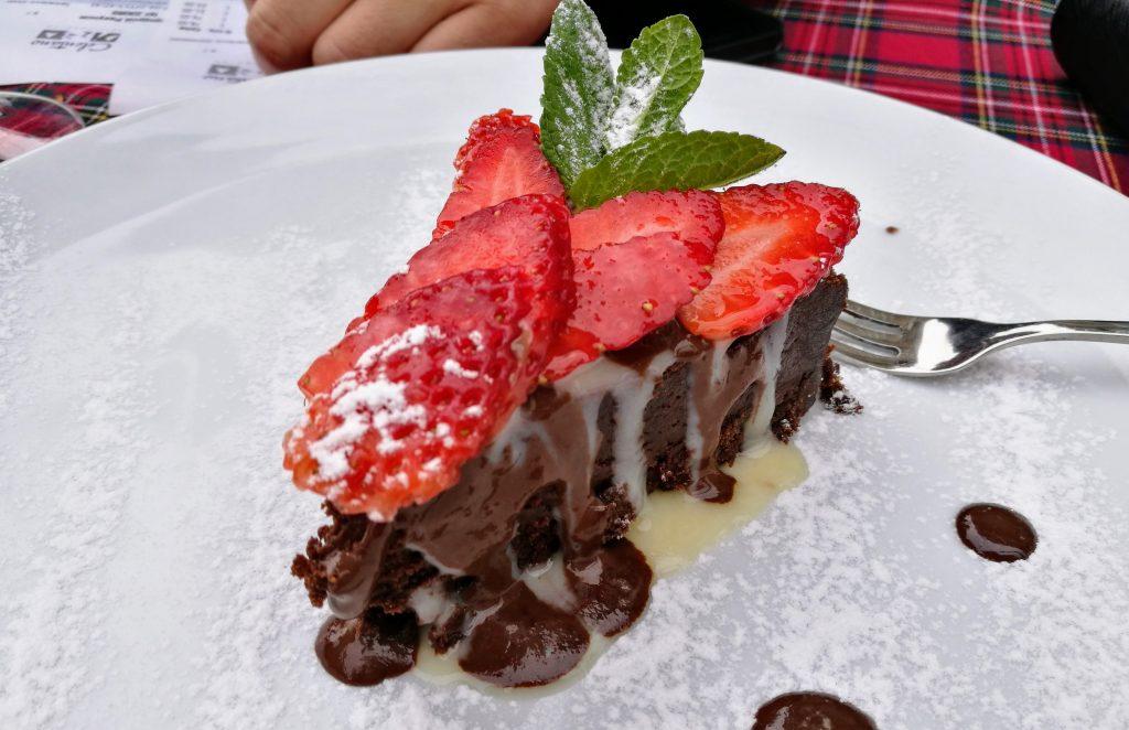 Brownie-Kuchen mit frischen Erdbeeren und Schokosoße im Celentano Ristorante